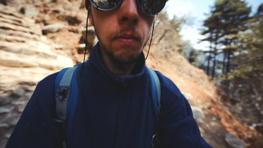 NAMCHE BAZAAR, NEPAL - MAY 6, 2016: Male trekker makes selfie, spins camera around while walk along the Namche Bazaar-Lukla path. On the way he meets porters and trekkers. The Himalaya #24350582