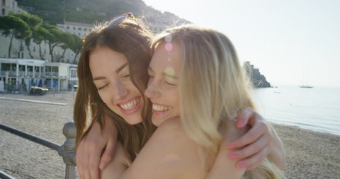 Best friends hugging each other giving kiss on cheek Tourist woman enjoying sunset on beach girlfriend travellers enjoy European travel adventure summer vacation Amalfi Coast Italy