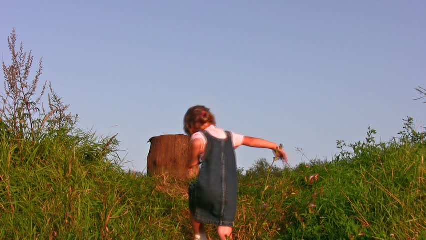 little girl climb on stump
