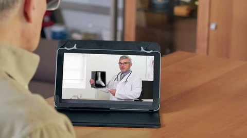 male doctor showing ankle x rays on a tablet video chatting with patient