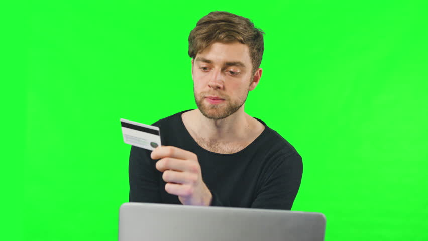 Close-up view of young man online shoping at home on pc, typing credit card number. Dolly shoot, Green Screen. Easy to key out and add your own background. | Shutterstock HD Video #24386342