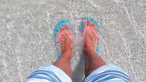 Male feet on the beach at seaside, high up view. Man wearing flip flops standing on the seashore with water covering the feet. Summer and relax concepts.