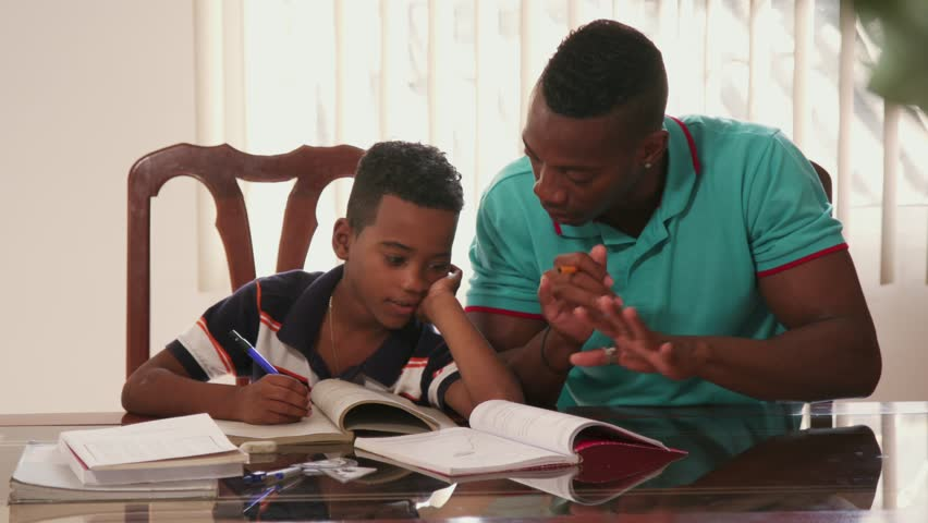 Happy black family at home. African american father and child. Hispanic dad helping son with school homework. Education and relationship, man teaching and boy learning