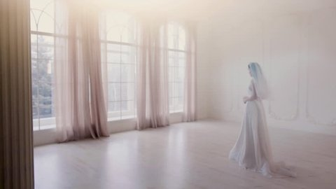 Beautiful Bride goes towards the large window in the bright room in slow motion