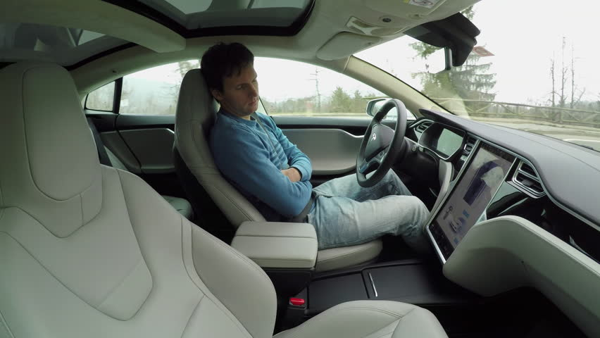 KARLSRUHE, GERMANY - FEBRUARY 1st 2017: Male driver sleeping behind the self-driving steering wheel of a autonomous electric Tesla car. Man fell deeply asleep while driving along the countryside road