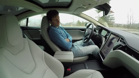 AUTONOMOUS TESLA CAR, FEBRUARY 2016:  Male driver sleeping behind the self-driving steering wheel of a autonomous electric Tesla car. Man fell deeply asleep while driving along the countryside road