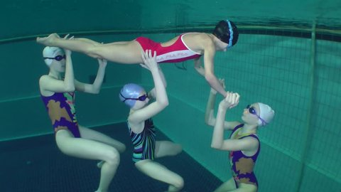 NIKOLAEV, UKRAINE - JANUARY 2017: Synchronized swimming, team training, support, underwater, the camera lifted above the water surface.