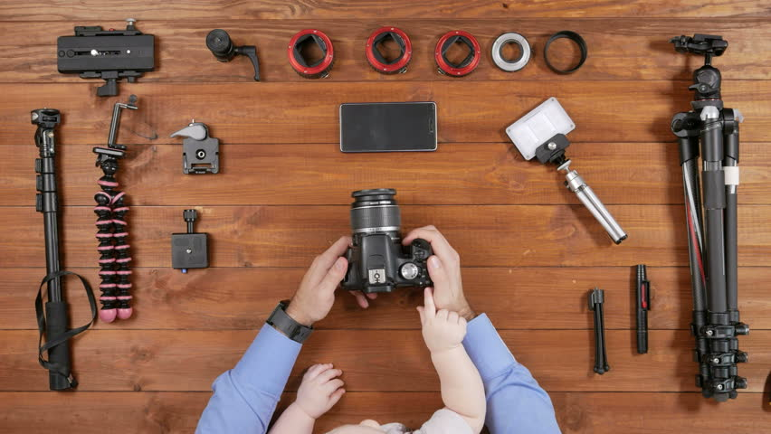 Photographer father with a young son checked the camera before shooting. Wooden table top view. Toddler touching a button. Equipment for shooting on the table. | Shutterstock HD Video #24522413