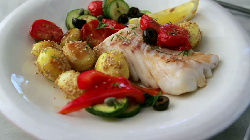 A meal of fish on a plate with potatoes and tomatoes. Fork picking up a potato.