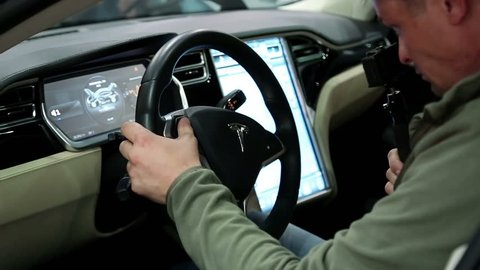 UKRAINE, KIEV, JUNE 10, 2016: Exhibition of electric cars. Man inside Tesla electromobile. Tesla electromobile interior