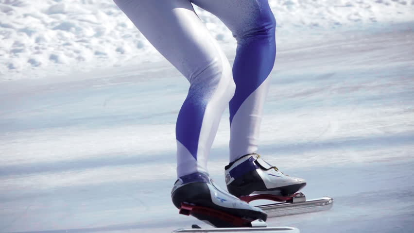 Speed ice skater skating on outdoor race on turn HD slow-motion video. Close-up view of professional athlete legs training for winter olympic. Lower body back view.