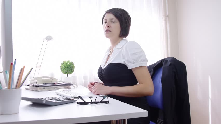 Overworked tired business woman rubbing back, belly, modern office