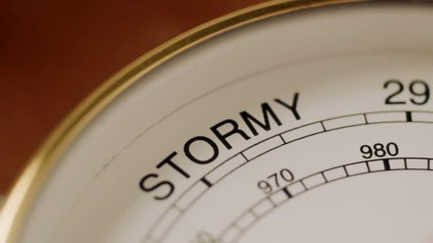 Barometer needle swings to indicate stormy weather