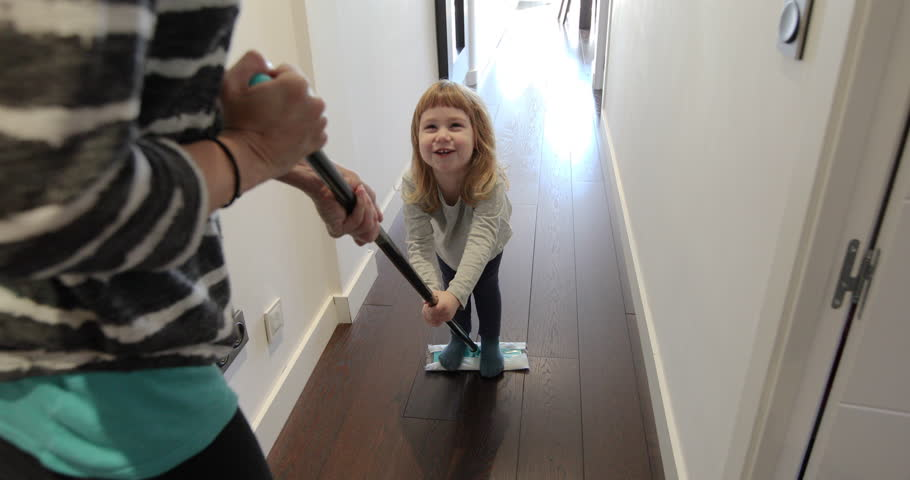 Funny scene of three years old laughing child sliding on flat dust mop while woman sweeping the floor in corridor at home    Shutterstock HD Video #24560732