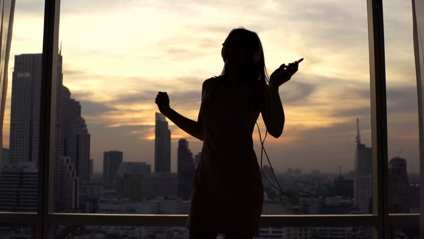 Woman dancing while listening to music on cellphone by window, super slow motion 120fps