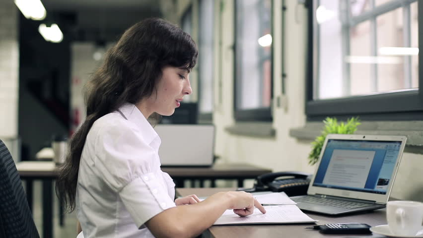 Businesswoman working with documents and laptop in the office