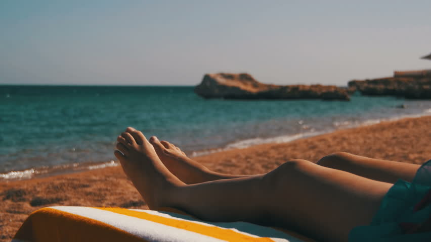 Legs of Woman Lying on Beach Sun Lounger near the Red Sea, Egypt. Woman lie on the lounger at the sandy beach in Egypt, overlooking the Red Sea. Young woman relaxing in the chaise lounge on a resort.