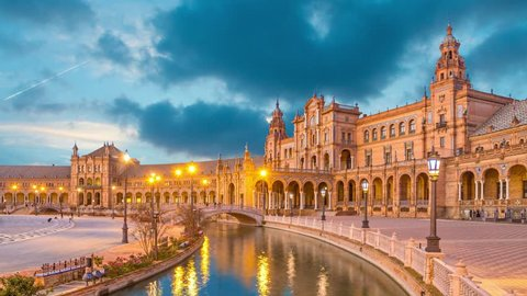 Canal and bridge reflecing in water on Plaza de Espana in the evening, Seville, Andalusia, Spain  (static image with animated sky)
