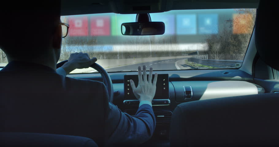 A businessman riding in a futuristic car and following a conference of economics and finance while driving. The call appears in augmented reality with projection of holograms. | Shutterstock HD Video #24631502