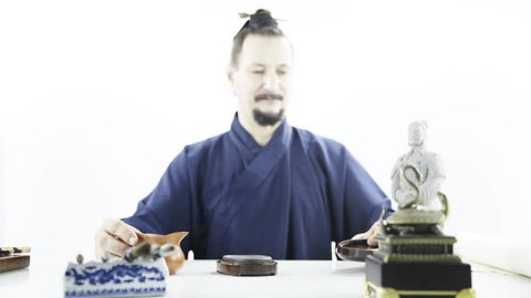 Caucasian person preparing for traditional Chinese calligraphy 4K. Wide shot dream-like of male person in focus wearing blue kimono and preparing calligraphy tools on white table.