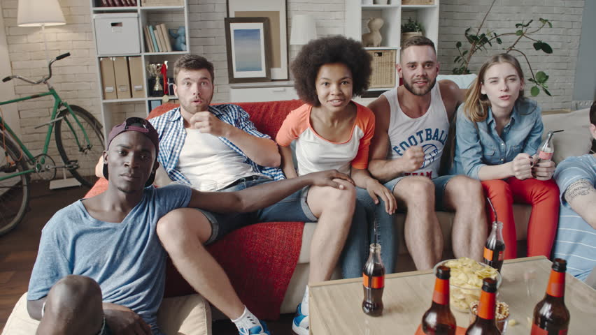 Slow motion shot of young friends watching match on TV at home, yelling at camera, raising up hands and jumping while celebrating victory of favorite team | Shutterstock HD Video #24648374