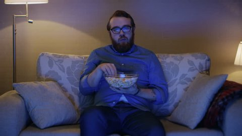 Portrait Shot of a Man Sitting on a Sofa in His Living Room, Eating Popcorn and Watching TV. Floor Lamps are Turned ON. Shot on RED EPIC-W 8K Helium Cinema Camera.