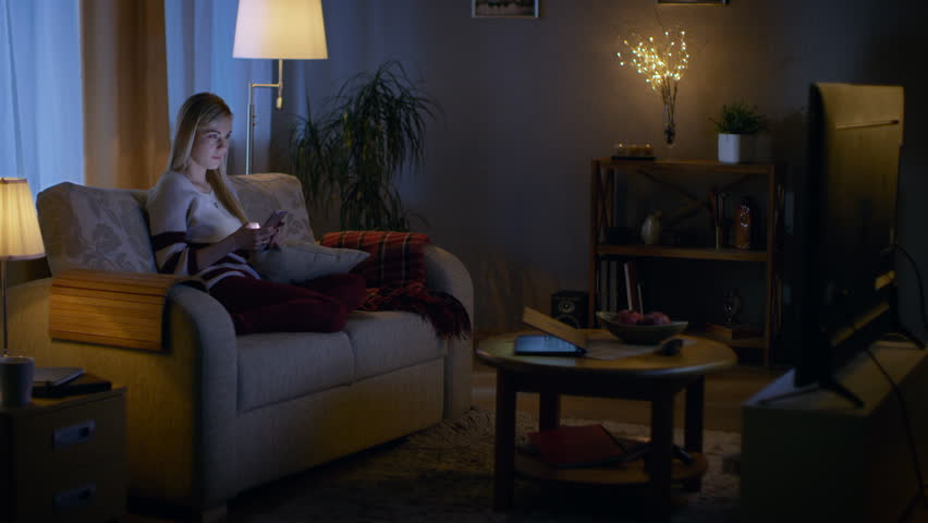 In the Evening Beautiful Young Woman Relaxes on a Couch in Her Cozy Living Room. She Uses Her Smartphone and Simultaneously Watches TV.  Shot on RED EPIC-W 8K Helium Cinema Camera. | Shutterstock HD Video #24653912