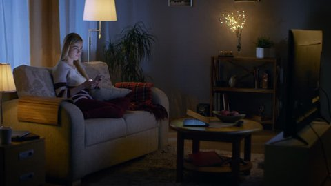 In the Evening Beautiful Young Woman Relaxes on a Couch in Her Cozy Living Room. She Uses Her Smartphone and Simultaneously Watches TV.  Shot on RED EPIC-W 8K Helium Cinema Camera.