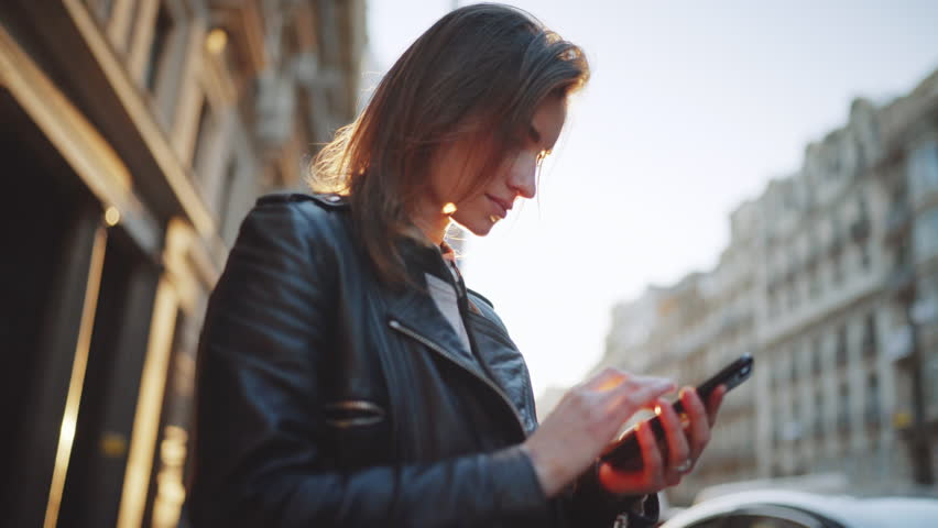 Side view of young hipster girl wearing leather jacket and chatting with friends at social networks via smartphone, sunlight background | Shutterstock HD Video #24654362