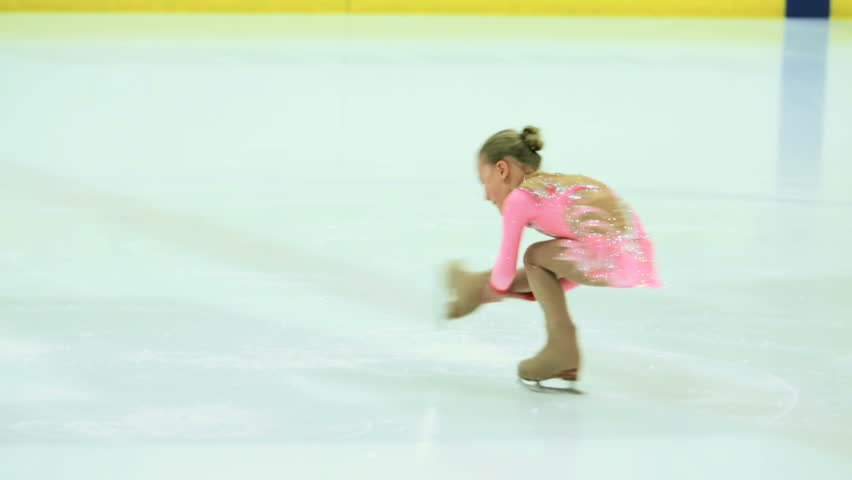 Little girl figure skating at the indoor ice arena.