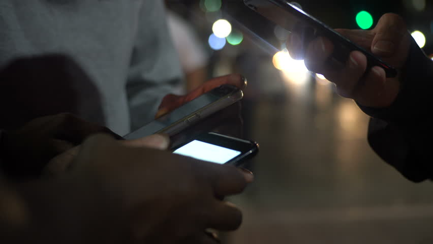 Group of friends checking social media using app on smart phone at night in city