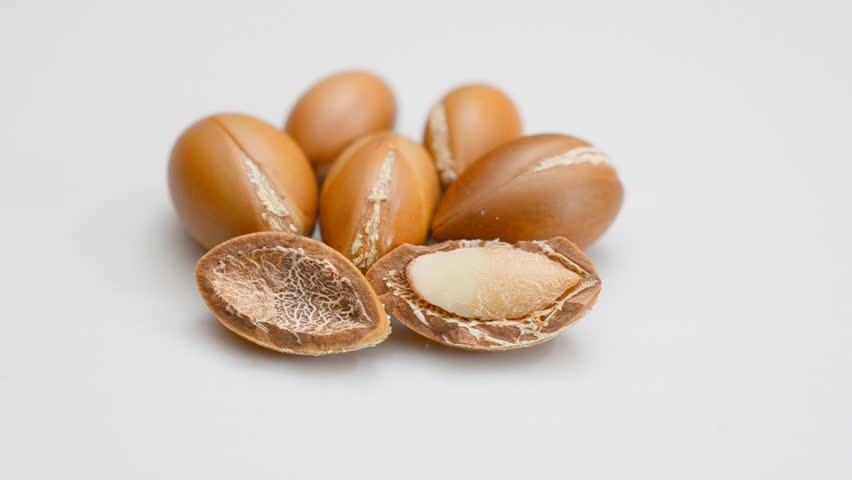 Argan seed rotate on white table.