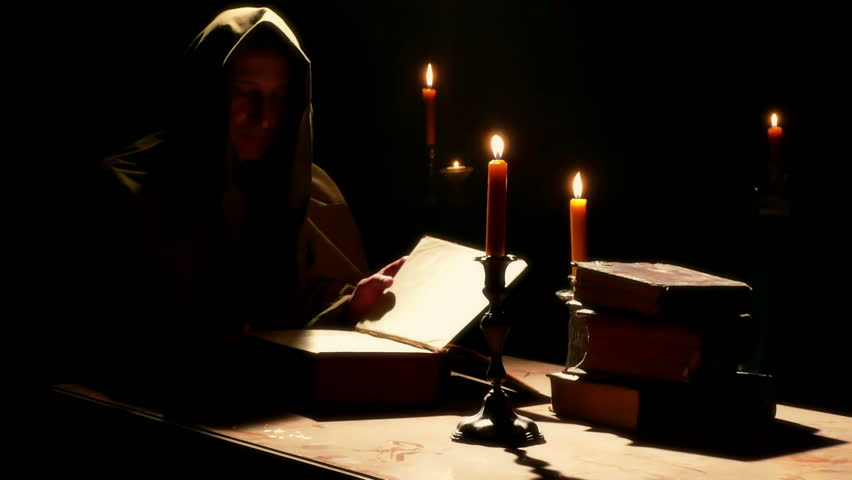 Monk reads the Old Liturgical Book ; Monk reads the old liturgical book in the monastery cell under candlelight