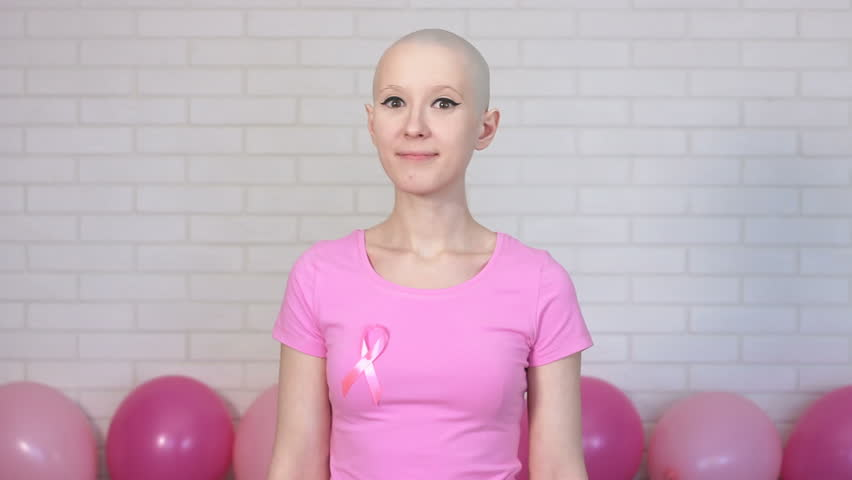 Confident breast cancer survivor woman looking crosses her arms looking at the camera and smiling - breast cancer awareness concept