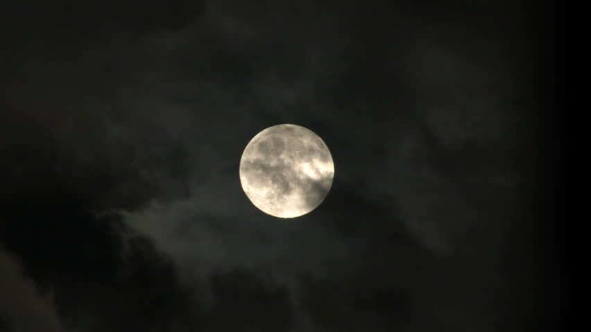 Clouds pass in front of a full moon