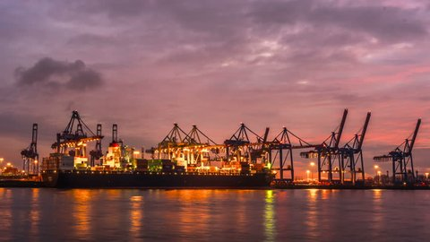 Container ship unloading in the sunset, time lapse