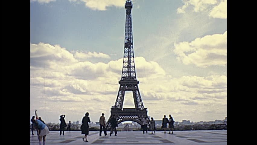 Paris Eiffel Tower panorama from Palais de Chaillot palace. Jardins du Trocadero gardens with tourists looking. Historic restored footage on 1976 in France. Parisians in vintage fashion clothing.