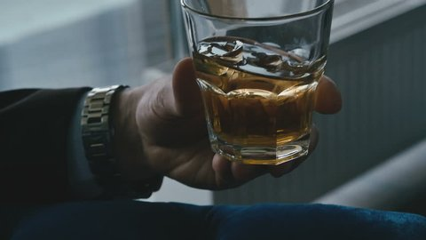A man holding a glass of whiskey and ice cubes in close-up