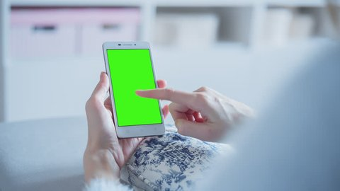 Young Woman sitting on a couch uses SmartPhone with pre-keyed green screen. Few types of motion - scrolling up and down, tapping, zoom in and out. Perfect for screen compositing. 10bit ProRes 444.