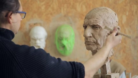 Sculptor modelling sculpture adjusting face details head made of clay. Creative concept.