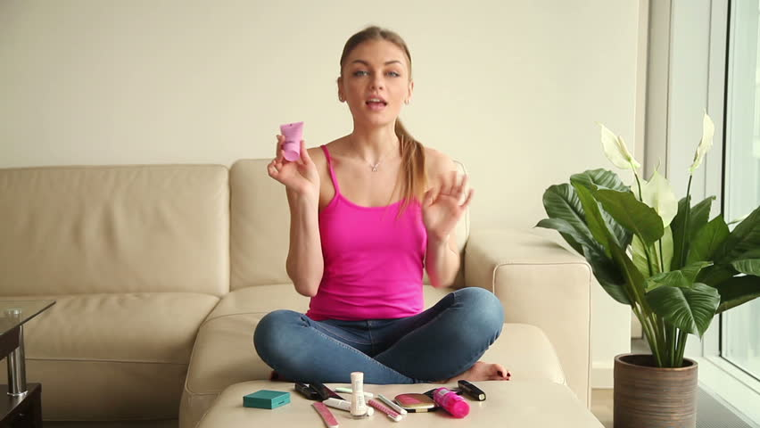 Young beautiful funny blogger lady self recording video for vlog about cosmetics she uses. Casual female vlogger sitting on sofa in living room at home, talking, presenting beauty products on camera