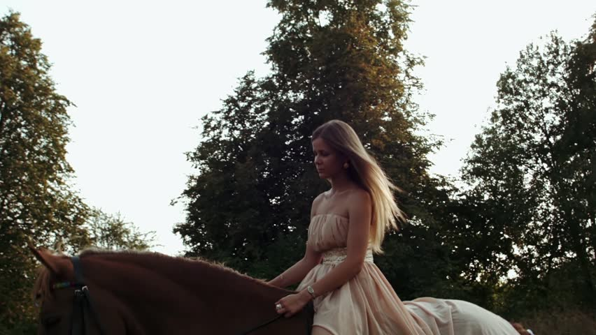 Girl Rides On a Brown Horse In a Meadow. Girl In Dress Riding On a Brown Horse In The Field. Young Woman Rides In a Meadow With Summer Sunlight. Girl With a Horse. Woman On The Horse.