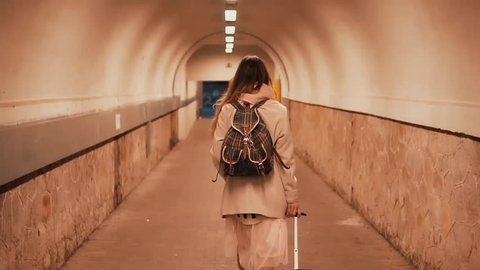 Young woman walking through the tunnel carrying the suitcase. Girl with backpack arrives in the city and goes in hotel.