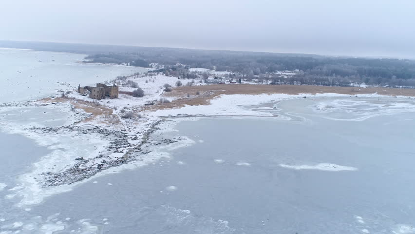 The small Toolse castle in the middle of the winter with the frozen ground surrounding the castle seen on an aerial view