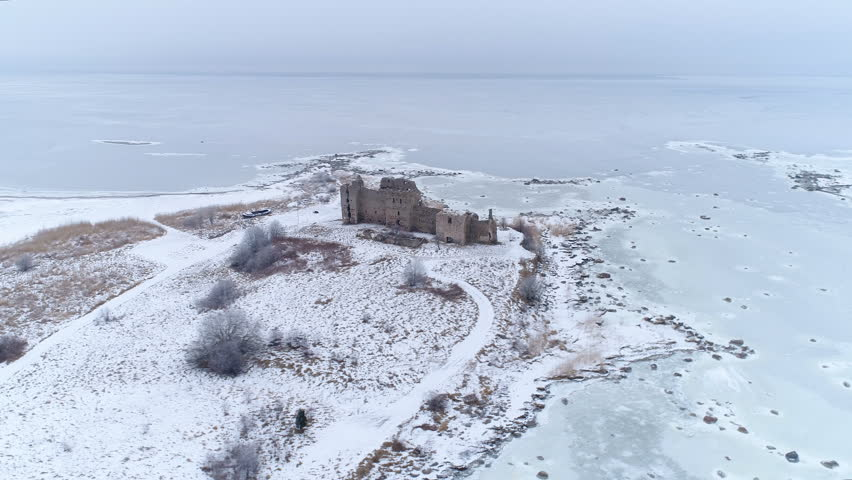 Aerial scenic view of the frozen sea in Lahemaa with the Toolse caslte in the middle of the icey ground in a winter season