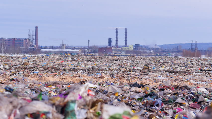 Garbage dump. Industrial factory on a background. Enviroment pollution concept.