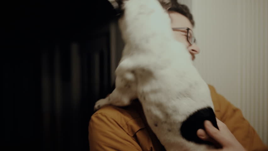 Happy dog licks mans face.