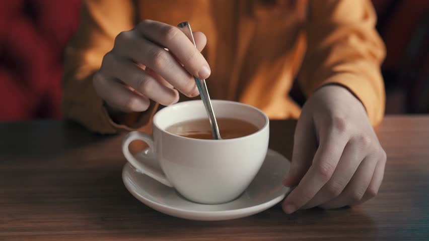 A woman stirs sugar in tea with a spoon in a white mug | Shutterstock HD Video #24829280