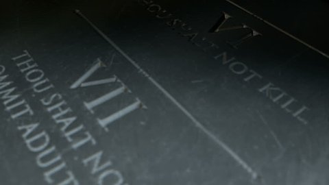 A slow close up pan across a stone tablet with the first five of the ten commandments inscribed onto them