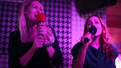 Two joyful women singing and dancing in karaoke club